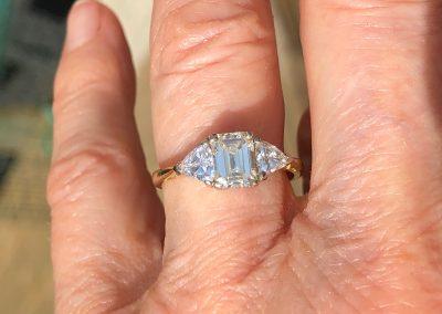 Unusual emerald cut diamond ring flanked by triangular diamonds