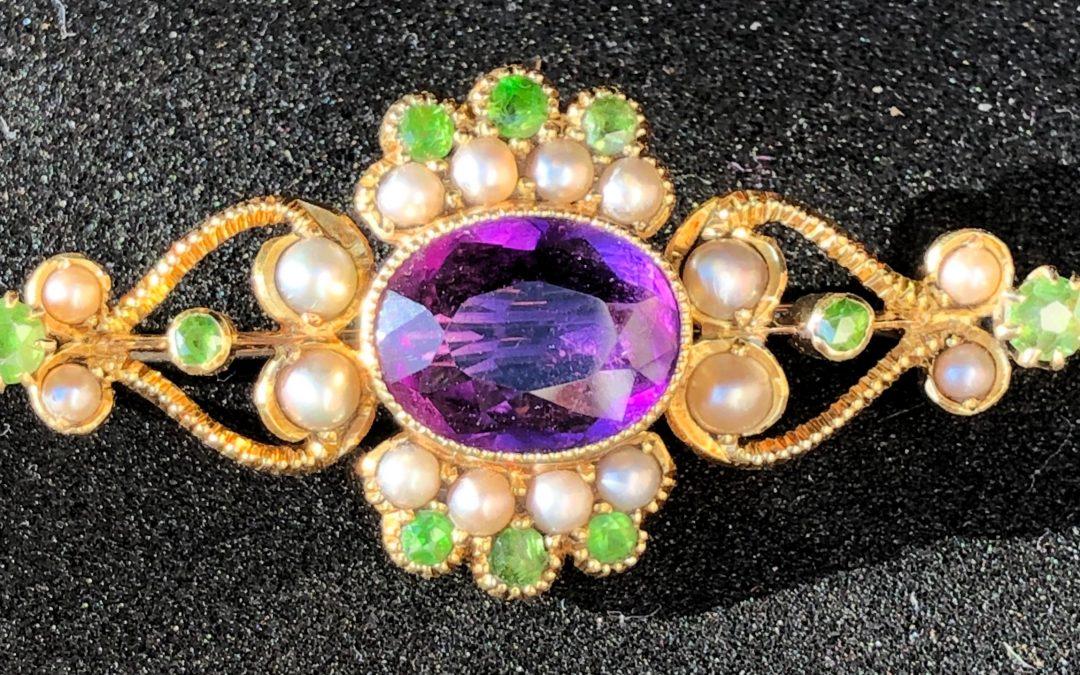 Pretty Suffragette brooch in 15 carat gold with demantoid garnets